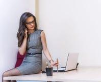 放松谈话在电话和使用她的膝上型计算机的女商人 库存照片