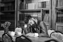 放松,休闲,茶时间 成熟人在时髦的内部坐并且喜欢放松读书 正式成套装备的有胡子的人 免版税库存照片