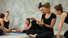 放松,使用smartphoe的三个少妇,谈话在锻炼以后在瑜伽类 股票录像