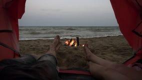 放松,说谎在海滩的红色帐篷里面的无忧无虑,青年人 男性和女性腿有海视图和篝火 股票视频