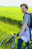 放松以绿色领域为背景的人骑自行车者 库存照片