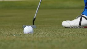 放球的职业高尔夫球运动员入孔 由孔边缘的高尔夫球与球员的在背景在一个晴天 免版税图库摄影