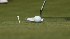 放球的职业高尔夫球运动员入孔 由孔边缘的高尔夫球与球员的在背景在一个晴天 免版税库存图片
