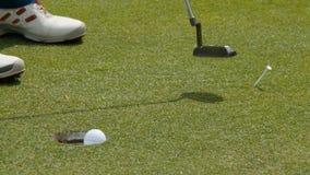 放球的职业高尔夫球运动员入孔 由孔边缘的高尔夫球与球员的在背景在一个晴天 免版税库存照片