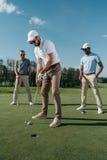 放球的高尔夫球运动员入孔,当站立他的朋友后边时 库存图片