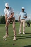 放球的高尔夫球运动员入孔,当站立他的朋友后边时 库存照片