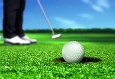 放球的高尔夫球运动员入孔 免版税库存图片