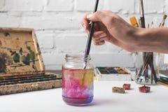 放画笔的艺术家入玻璃瓶子用水在工作场所 库存图片