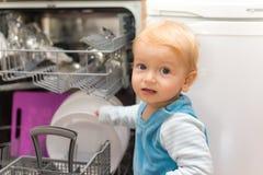 放盘的小男孩入洗碗机 库存照片