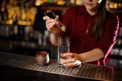 放石灰的女性侍酒者入玻璃 免版税库存图片