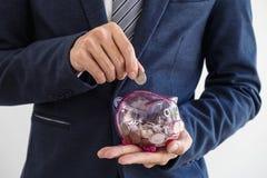 放硬币的商人入存钱罐,财政和investm 免版税库存图片