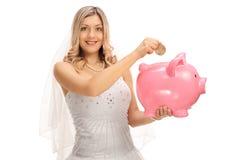放硬币的年轻新娘入piggybank 免版税库存照片
