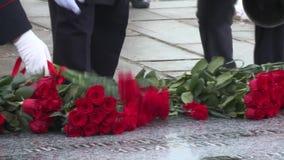 放红色花在纪念品 庆祝巨大爱国战争记忆  我们看人和他们的腿的仅手 影视素材