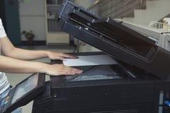 放纸片的妇女手入一个复制的设备 免版税图库摄影