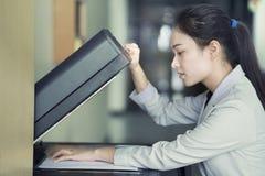 放纸片的妇女手入一个复制的设备 图库摄影