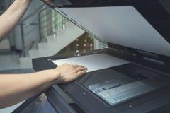 放纸片的妇女手入一个复制的设备 库存图片