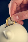 放置一枚欧洲硬币到贪心硬币银行里 免版税库存照片