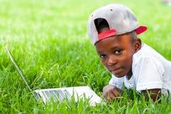 放置与膝上型计算机的非洲男孩在草 免版税库存照片