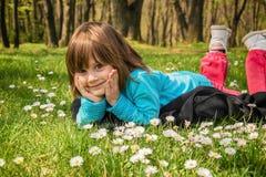 放置与面孔的小女孩在手在公园 免版税库存照片