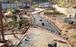 放置从一块黑砖的一条新的道路和红色大理石铺路石在一晴朗的秋天天在房屋建设站点 免版税库存图片
