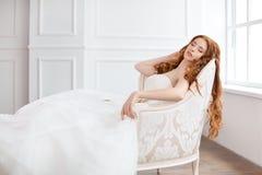 放置休息的美丽的礼服的新娘在沙发户内 库存照片