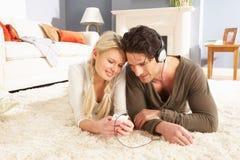 放置听的MP3播放器地毯的夫妇 图库摄影