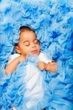 放置和睡觉在蓝色布料的非洲婴孩 免版税图库摄影