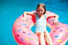 放置在一个五颜六色的可膨胀的多福饼的女孩 免版税库存图片
