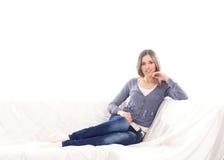 放置在一个空白沙发的牛仔裤的一个少妇 库存照片