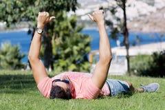 放置在一个绿色草甸的年轻人有海视图 使布赖顿椅子日甲板英国节假日懒人海边有风夏天的星期日靠岸 赞许 库存图片