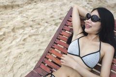 放置在一张木海滩睡椅的比基尼泳装的亚裔妇女 免版税图库摄影