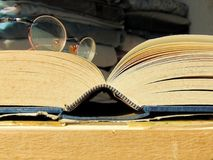 放置在一本老开放书的圆的葡萄酒玻璃 图库摄影