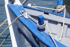 放置在一条老木小船的边的被打结的蓝色绳索 免版税库存图片