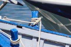 放置在一条老木小船的边的被打结的蓝色绳索 免版税库存照片