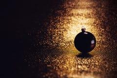 放置在一种欢乐金黄织品的黑暗的圣诞节球 库存图片