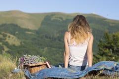 放置在一顿野餐的一条毯子的女孩在领域 图库摄影