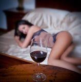 放置在与一杯的床上的神奇夫人红葡萄酒前景。在床上的肉欲的妇女和杯酒。美丽的女孩 库存图片