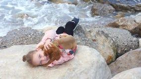放置在与她的甜小狗的岩石的女孩 股票视频