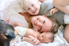 放置在与小孩儿子和新出生的婴孩的床上的愉快的母亲 免版税库存照片