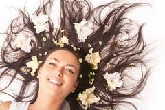 放置在与扩张的头发的地板的愉快的微笑的白种人深色的妇女画象  库存照片
