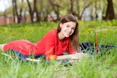 放置在与笔记本的草的美丽的女孩 免版税库存图片