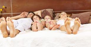 放置在与今后脚的床上的家庭 免版税库存照片