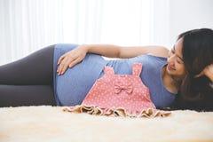 放置在与婴孩gir的床的美丽的怀孕的亚裔妇女 库存照片