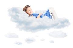 放置在云彩和看照相机的逗人喜爱的女孩 免版税库存照片
