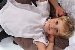 放置在他的爸爸的膝部和拥抱的一个可爱的微笑的甜小男孩 免版税库存图片
