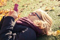 放置在公园和使用手机的十几岁的女孩 免版税库存图片