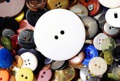放置在其他更小的五颜六色的按钮的大白色按钮 免版税图库摄影