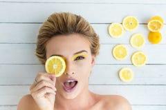 放置在切片的白肤金发的妇女柠檬旁边 免版税库存图片