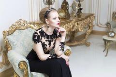 放置在华美的豪华礼服的一个减速火箭的沙发的美丽的白肤金发的皇家妇女 免版税图库摄影