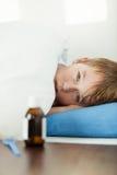 放置在厚实的毯子下的病的男孩在床 免版税库存照片